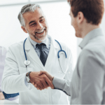 gastroenterology doctor greeting new patient with big smile & handshake